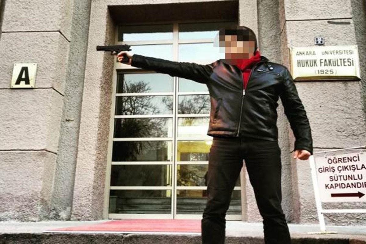 Yüzü blurlanmış M.A.V. isimli öğrenci Ankara Üniversitesi Hukuk Fakültesi önünde Siyasal Bilgiler Fakültesine silah doğrultuyor.