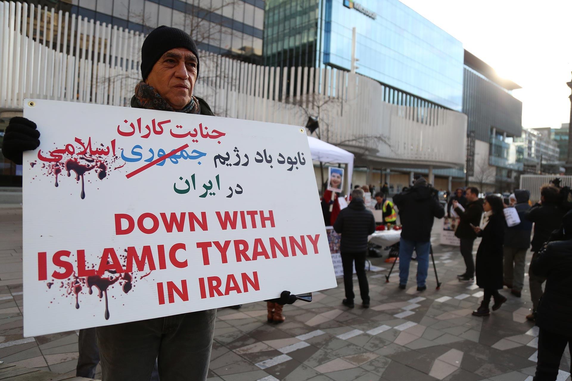 İran'ın Ukrayna uçağını düşürdüğünü itiraf etmesinin ardından sokağa çıkarak elindeki 'Down with Islamic tyranny in Iran' yazılı dövizle hükümet karşıtı eylemlere katılan bir İranlı