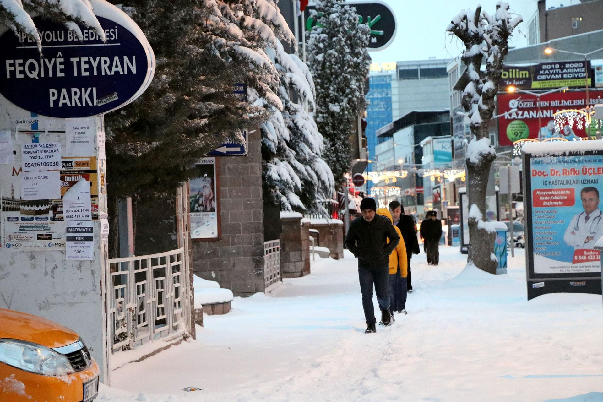 Van'ın İpekyolu ilçesinde kar yağışı altında yürüyenler