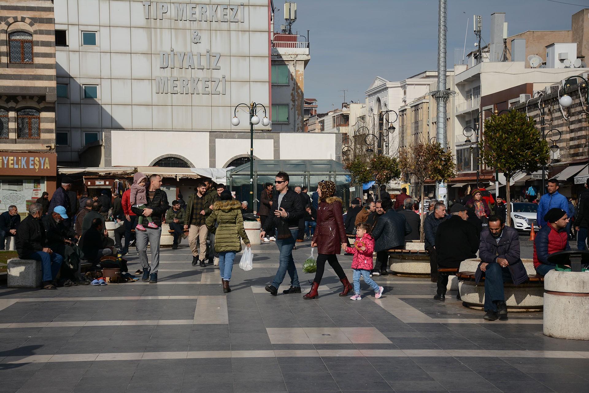 Diyarbakır'de bir meydanda oturan ve yürüyen çok sayıda kişi.