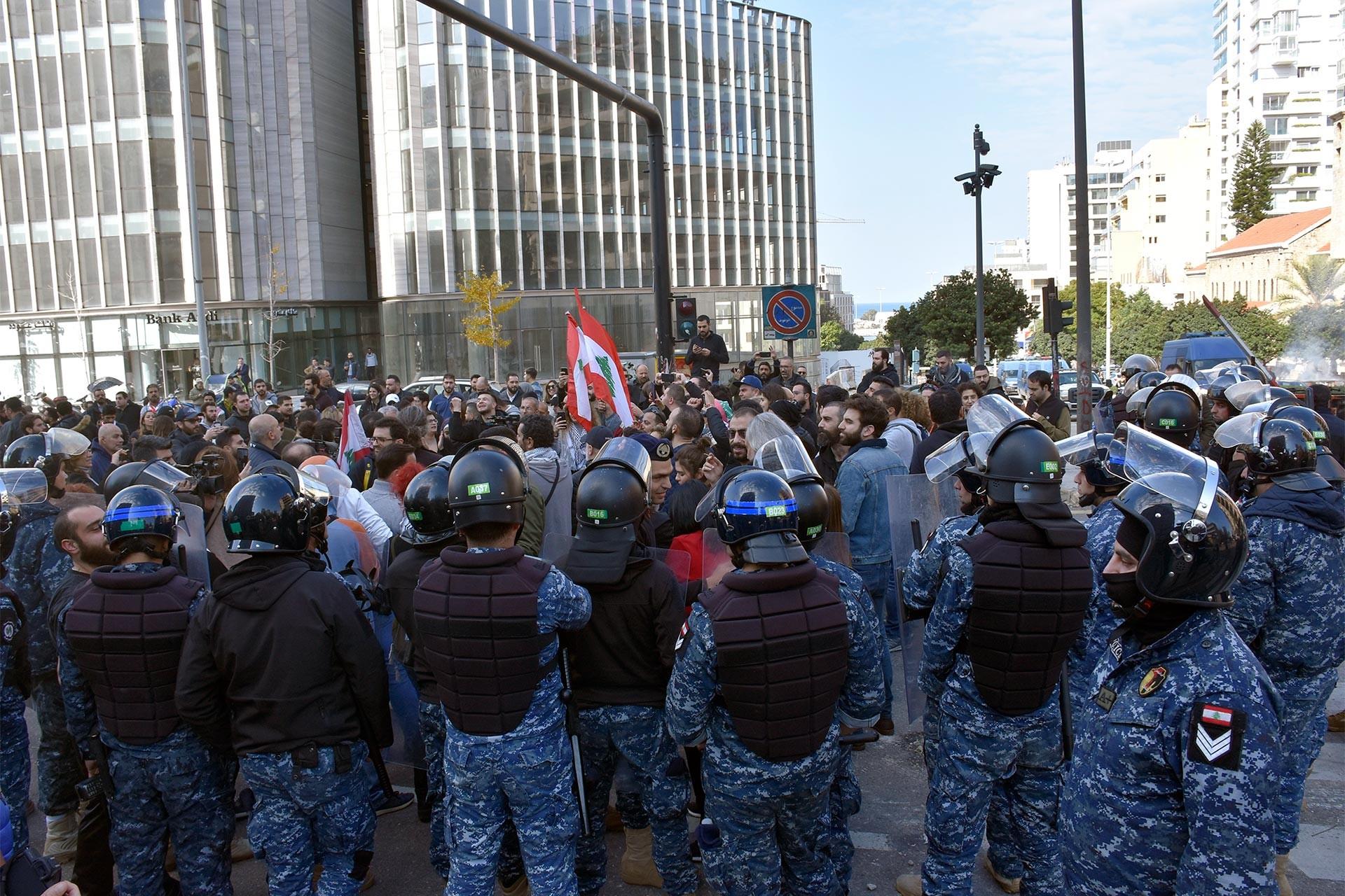 Lübnan'da protesto için toplanan halk ve onları çevreleyen polisler