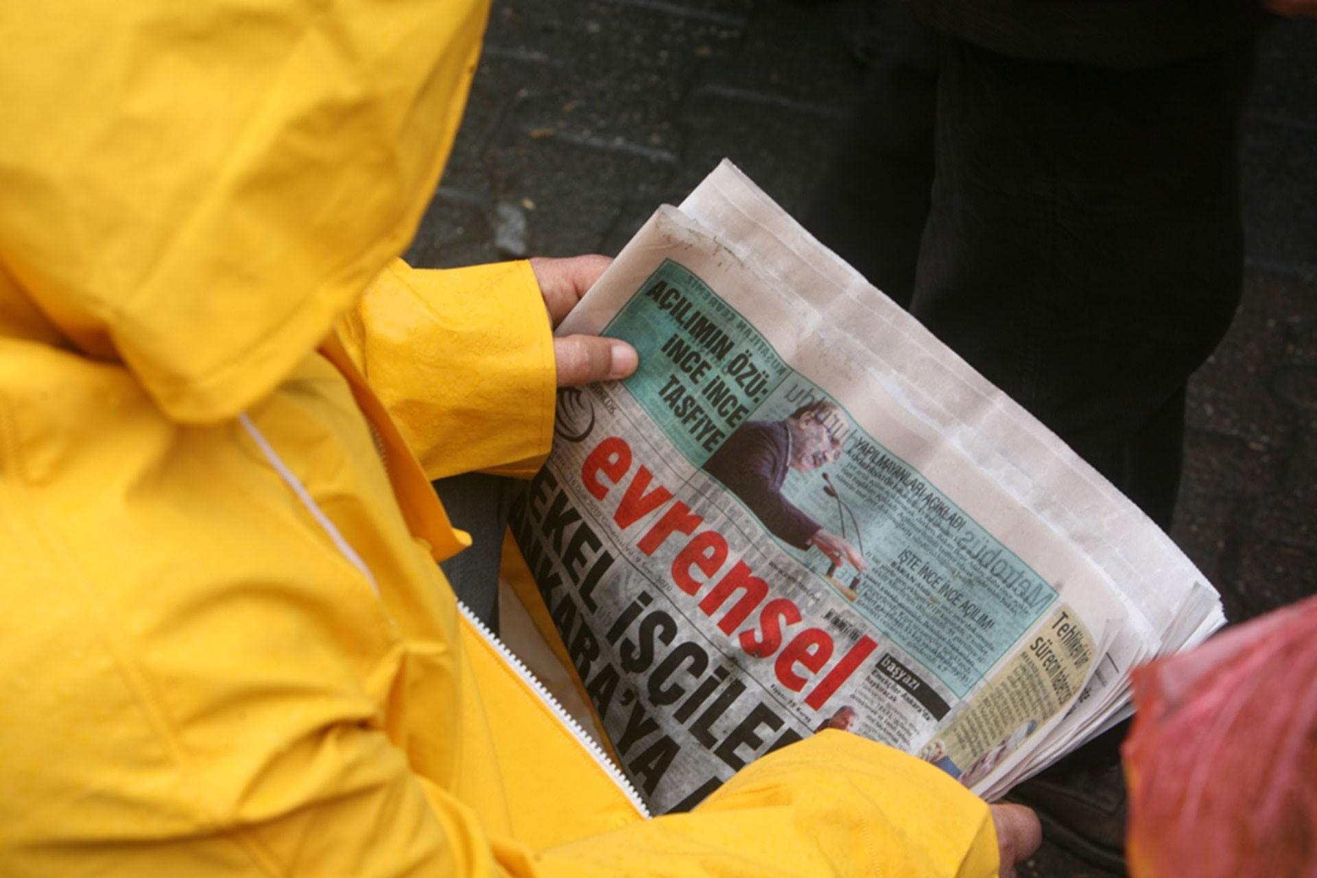 Evrensel gazetesi okuyan, sarı yağmurluk giymiş bir işçi