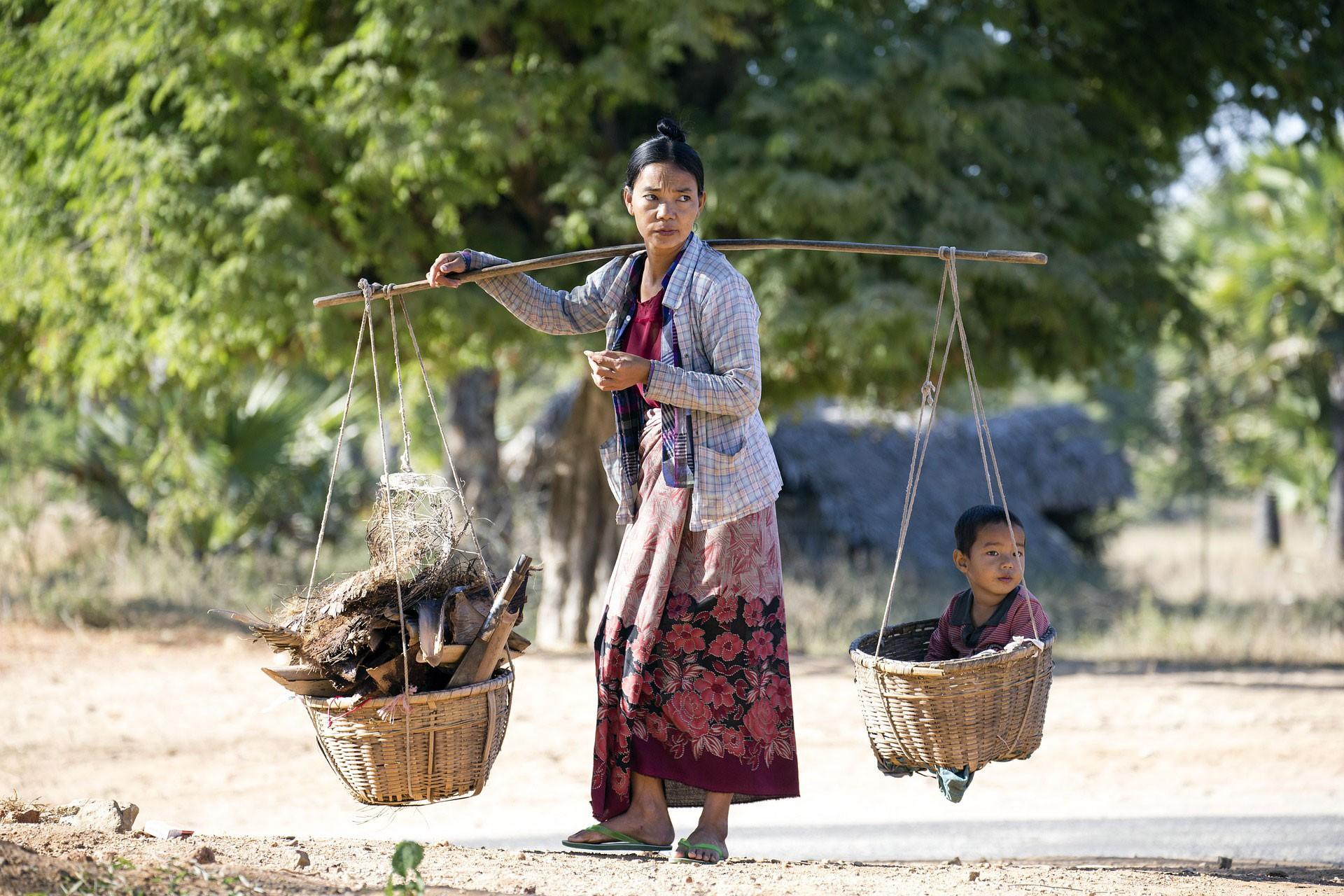 Myanmarlı bir kadın uzun bir çubuğa bağlı sepetlerin birinde odun, diğerinde çocuğunu taşıyor.