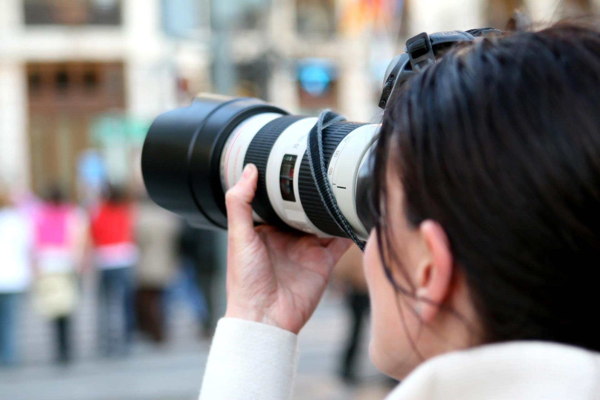 Fotoğraf makinesi ile fotoğraf çeken bir kadın
