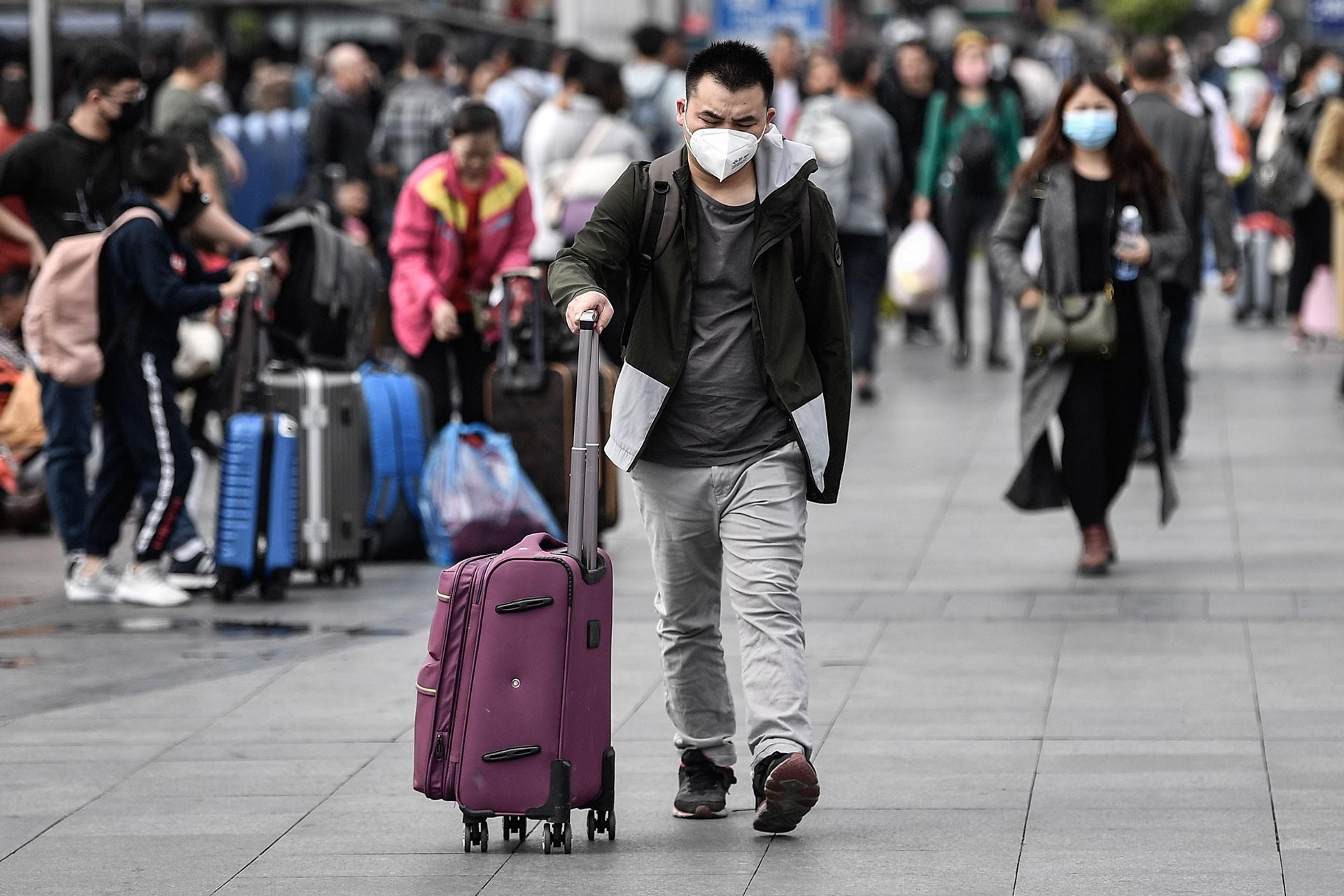Virüsten korunmak için maske takan bir Çinli, elinde valiziyle havalimanına gidiyor