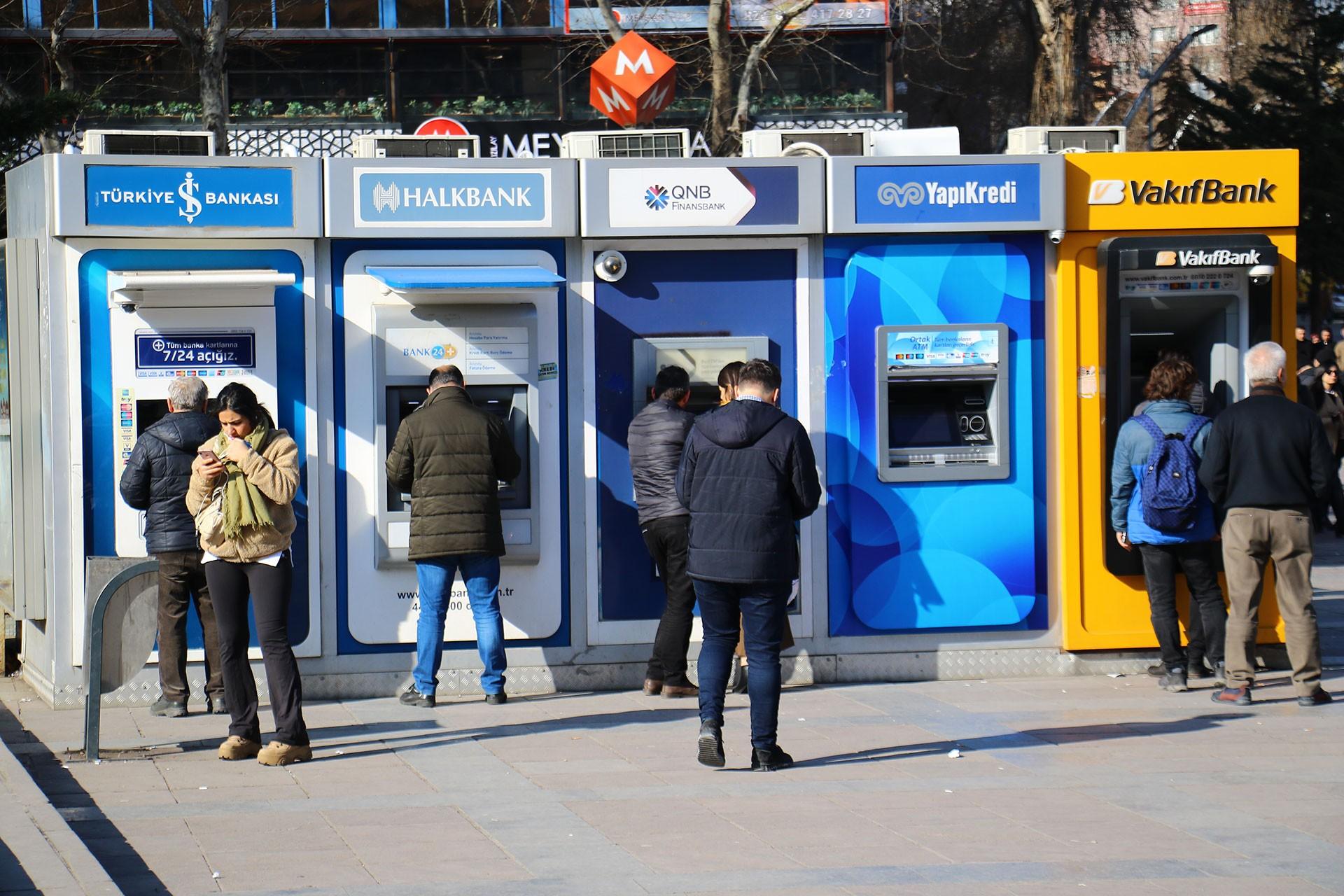 Bankamatiklerde sıra bekleyen yurttaşlar.