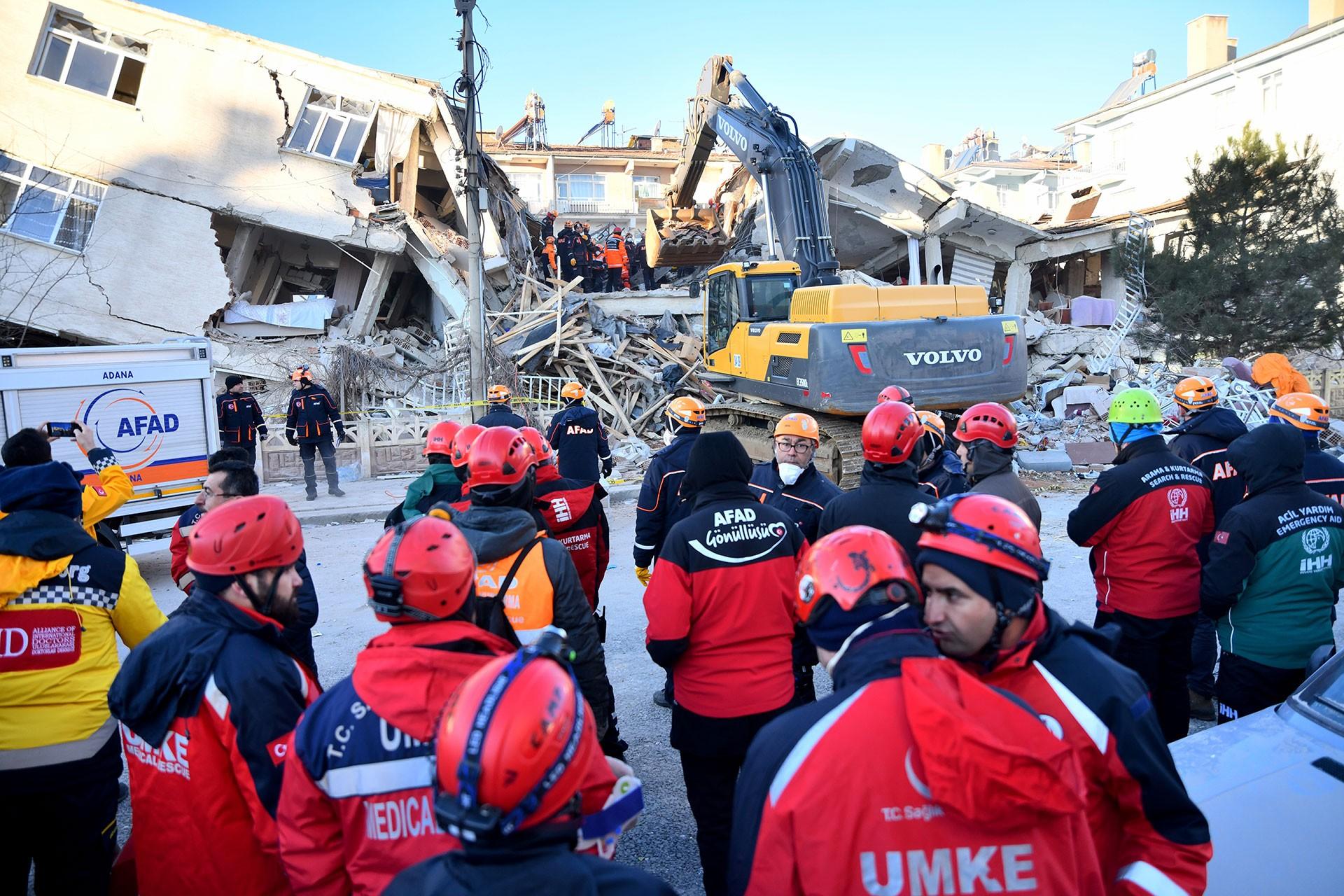 Yıkılmış binalar ve çalışma yürüten kurtarma ekibi.