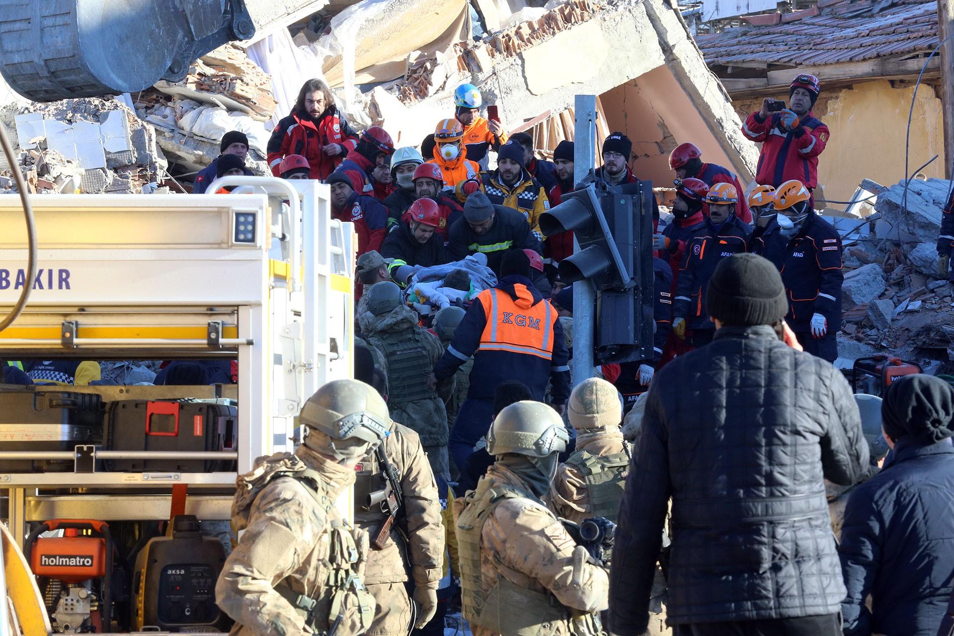 Ekipler, deprem sonucu yıkılan bir binanın enkazından küçük bir çocuğu çıkarıyor