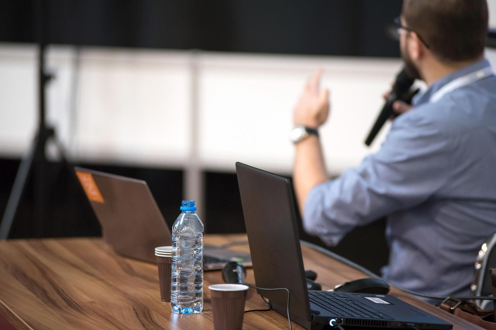 Masa üzerinde laptop ve su, konferans konuşması yapan bir erkek