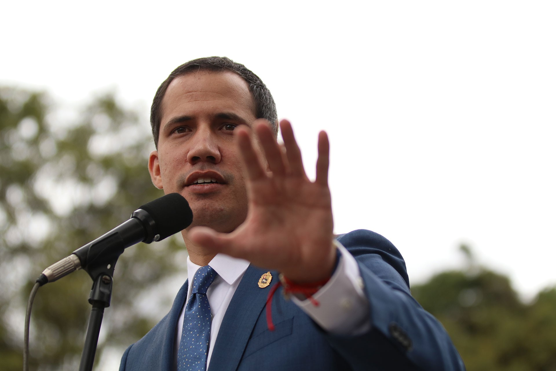 Juan Guaido gazetecilere açıklama yapıyor. Elini hayır anlamına gelecek şekilde kaldırmış.