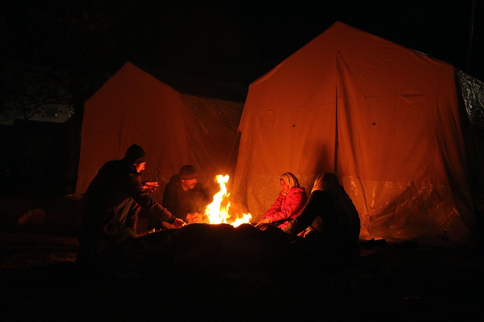 Elazığ'da çadır önünde yaktıkları ateş etrafında ısınmaya çalışan depremzedeler