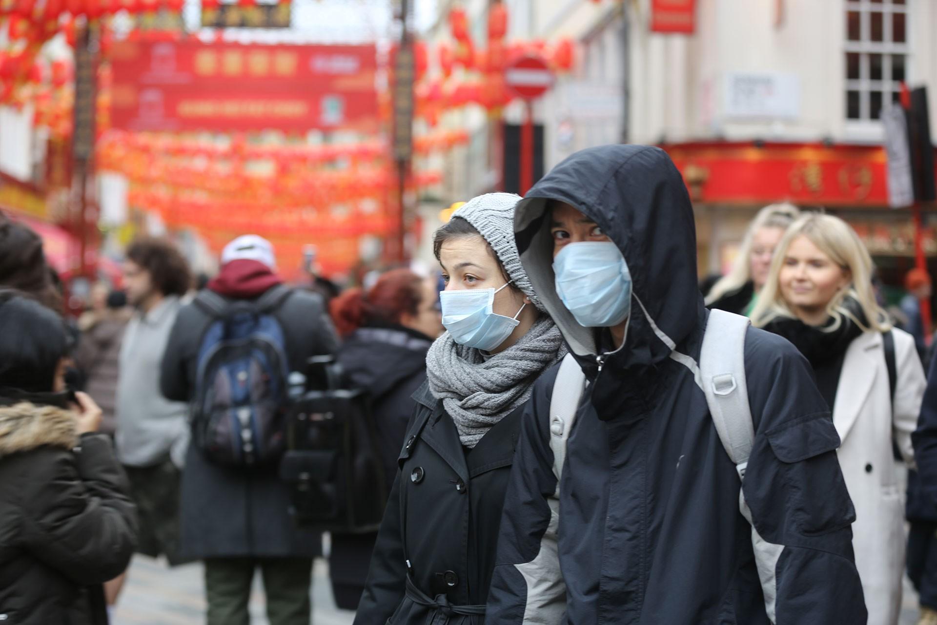 Koronavirüs salgını nedeniyle maske ile sokağa çıkan iki kişi