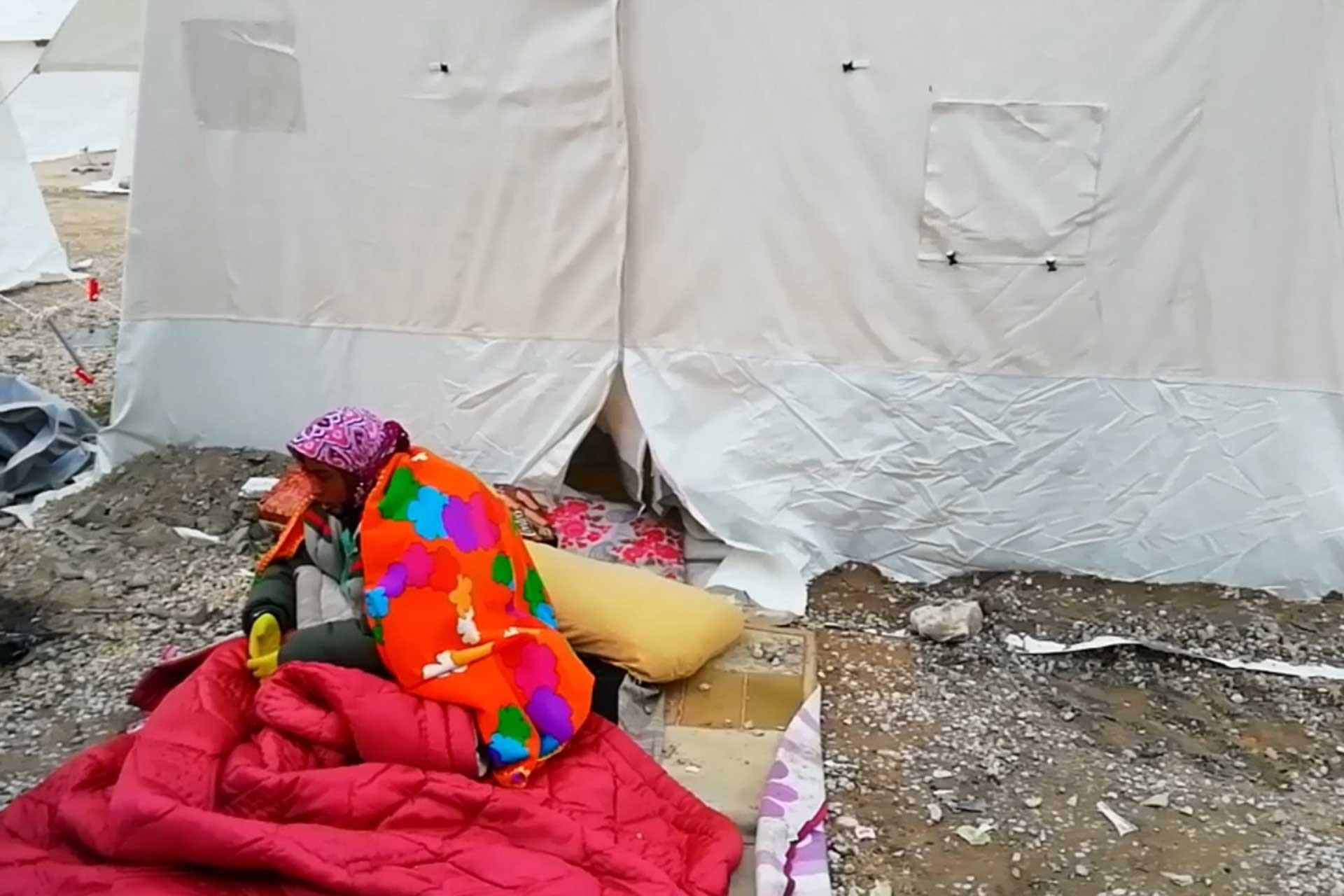 Çadır önünde battaniyeye sarılan bir kadın