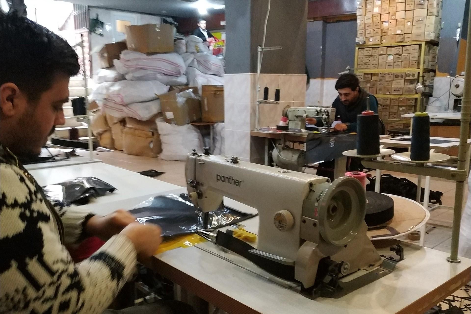 Tekstil atölyesinde makine başında çalışan işçiler