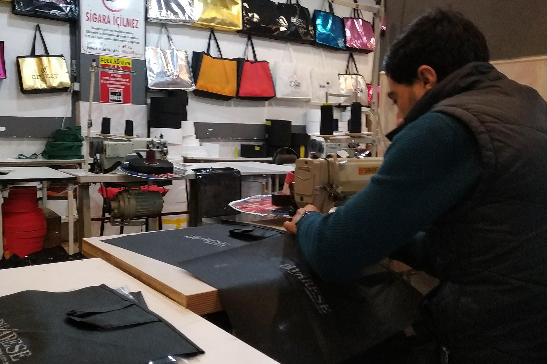 Tekstil atölyesinde makine başında çalışan işçi
