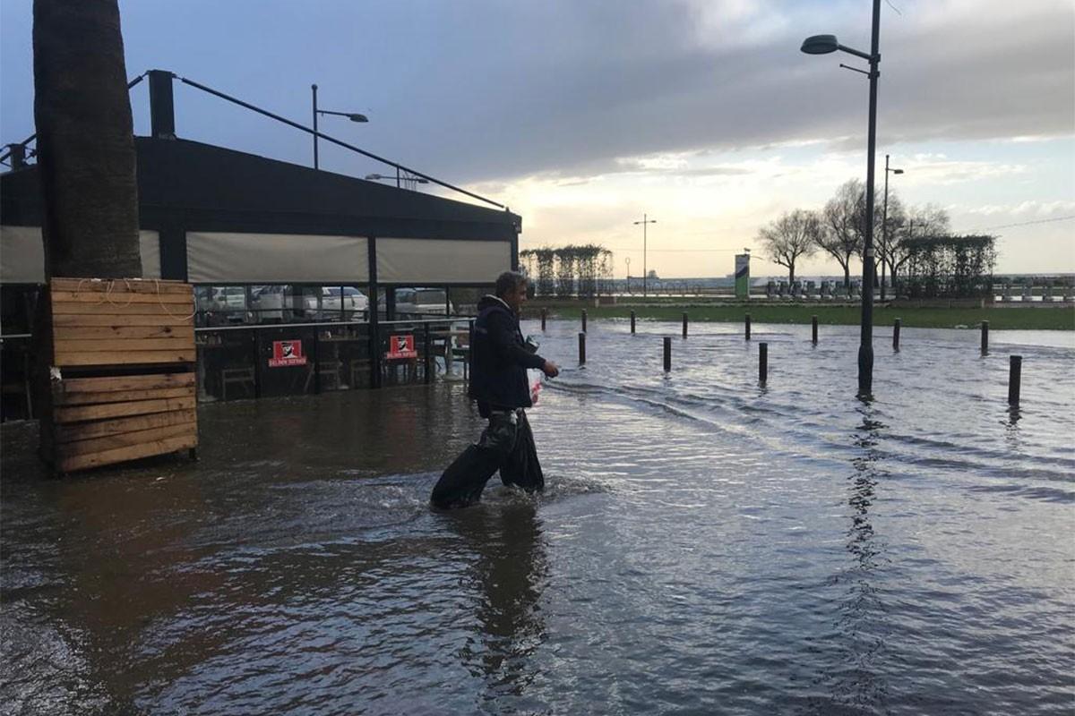İzmir'de sular altında kalan yolda yürümeye çalışan bir adam.