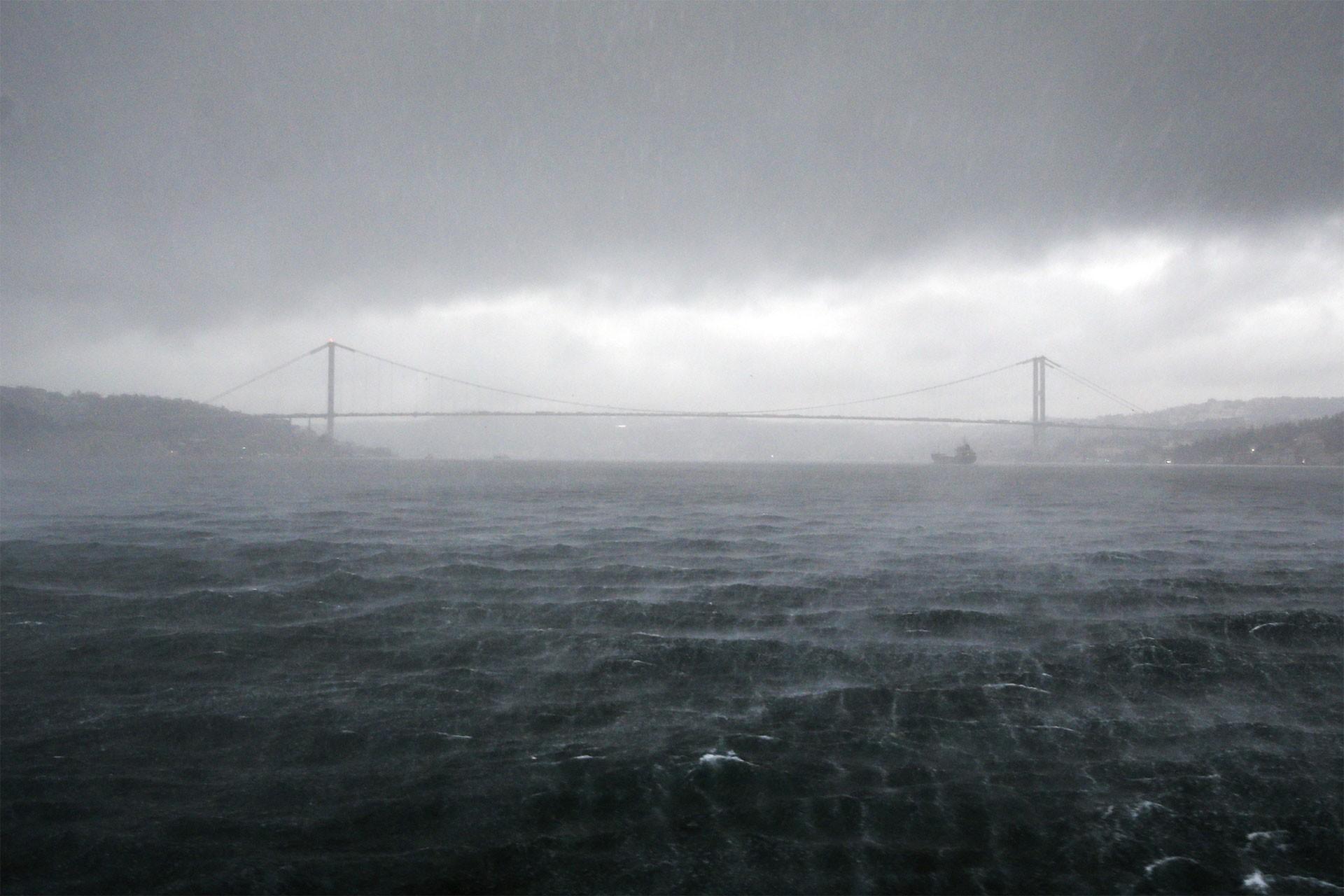 İstanbul'da sağanak yağış ve sisli bir görünümle boğaz köprüsü.