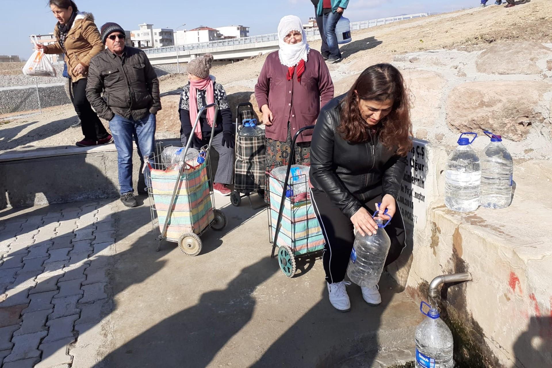 Çeşme başında su almak için sıraya girmiş insanlar