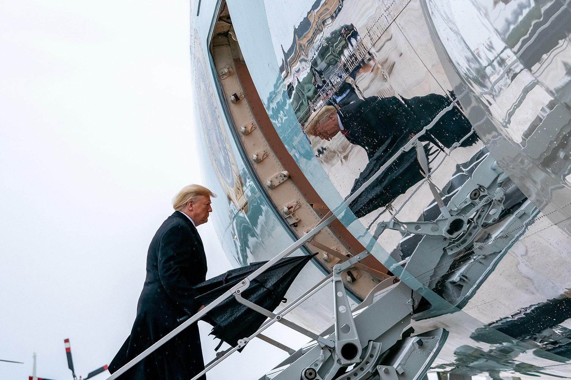 mp, uçağa biniyor, uçağın metalinde Trump'ın yansıması görülüyor.