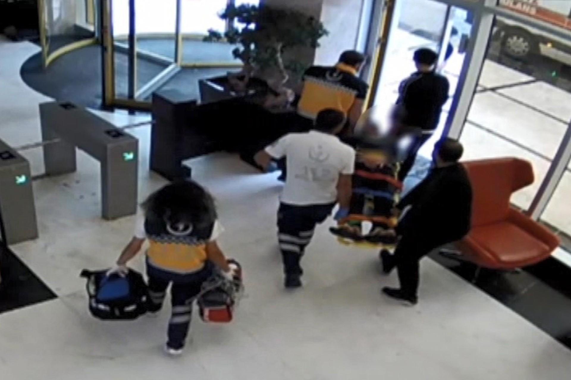 Sağlık çalışanları yaralı otel çalışanını taşıyor