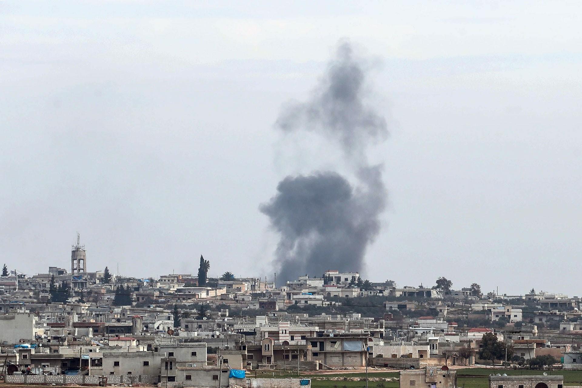 İdlib'de dumanlar yükselen bir mahallenin uzaktan görünümü.
