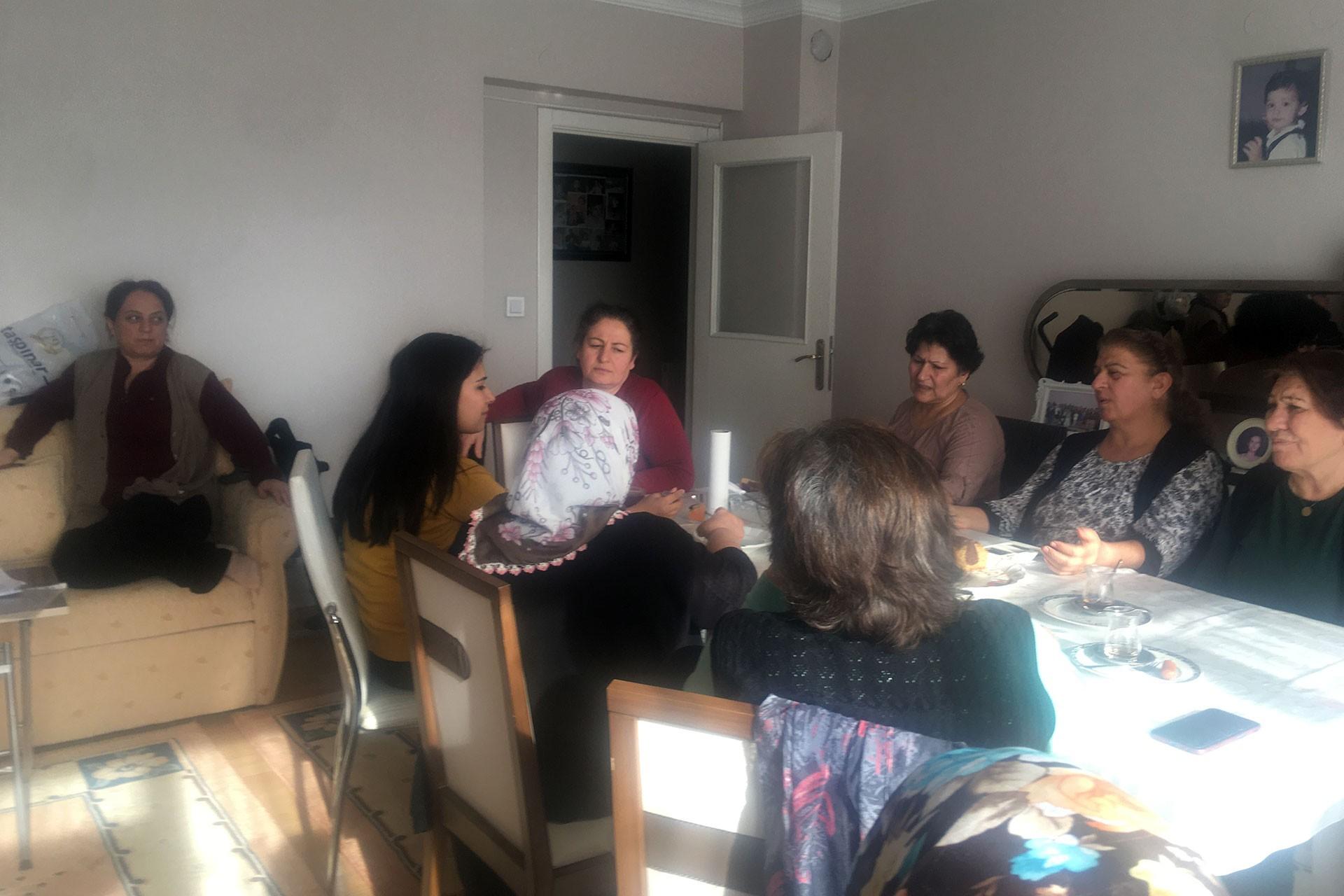 Masa başında oturan ve sohbet eden kadınlar.