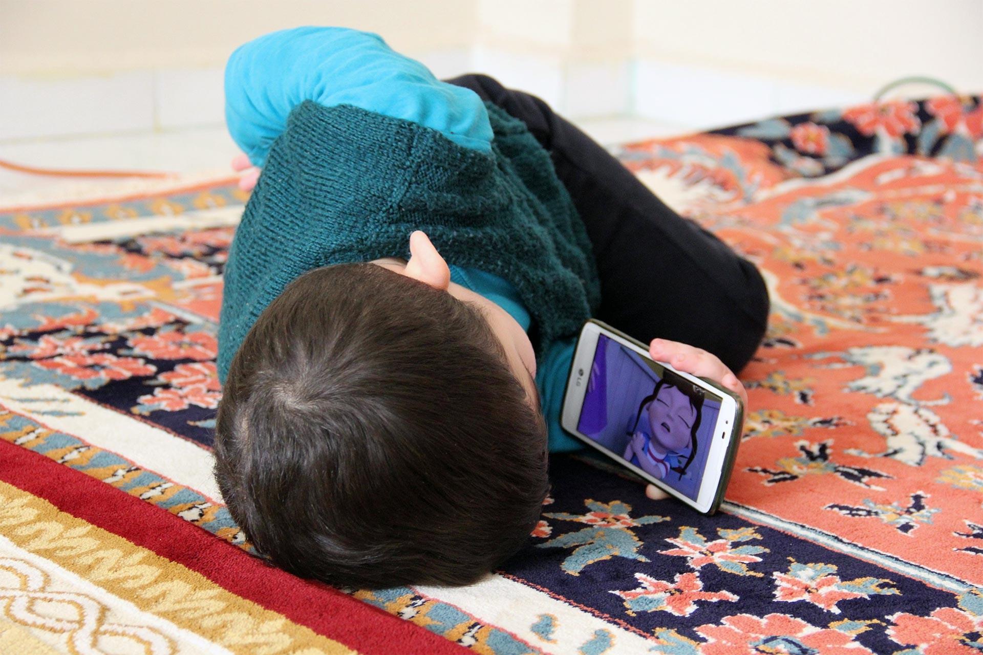 İlyas Gür cep telefonuyla çizgi film izlerken