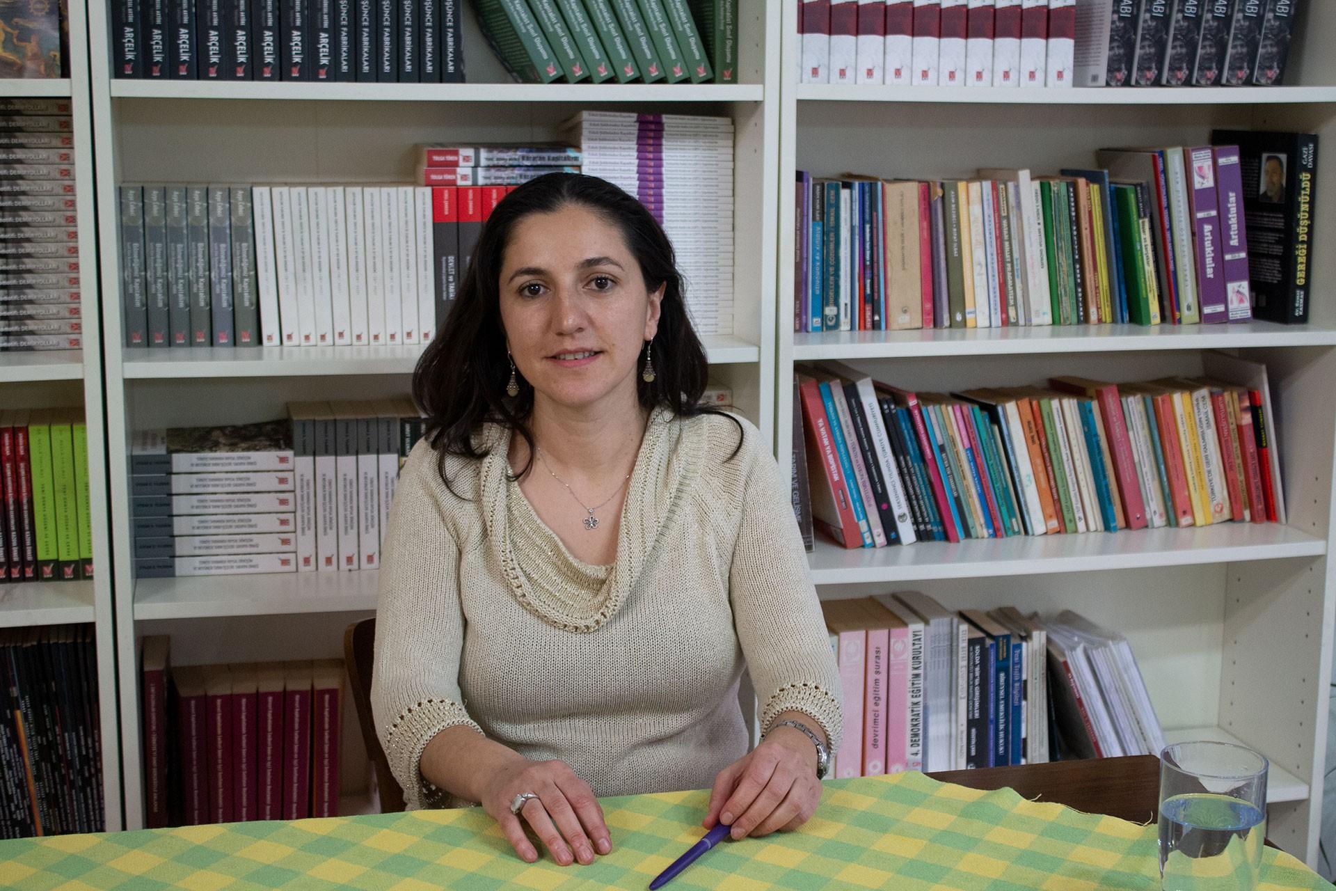 Dr. Selin Pelek bir kitaplığın önünde oturuyor