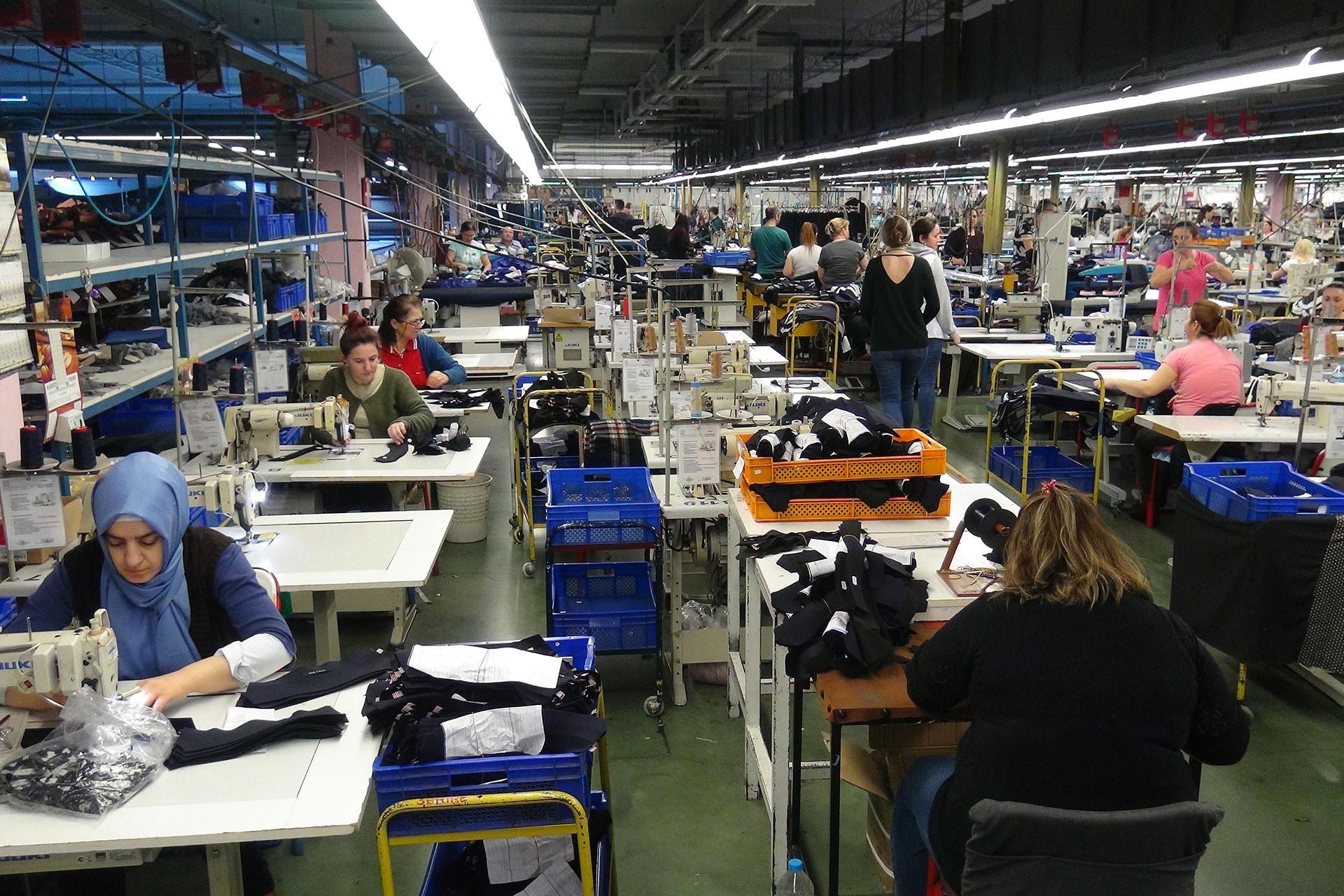 Kadın tekstil işçileri makinelerinin başında.