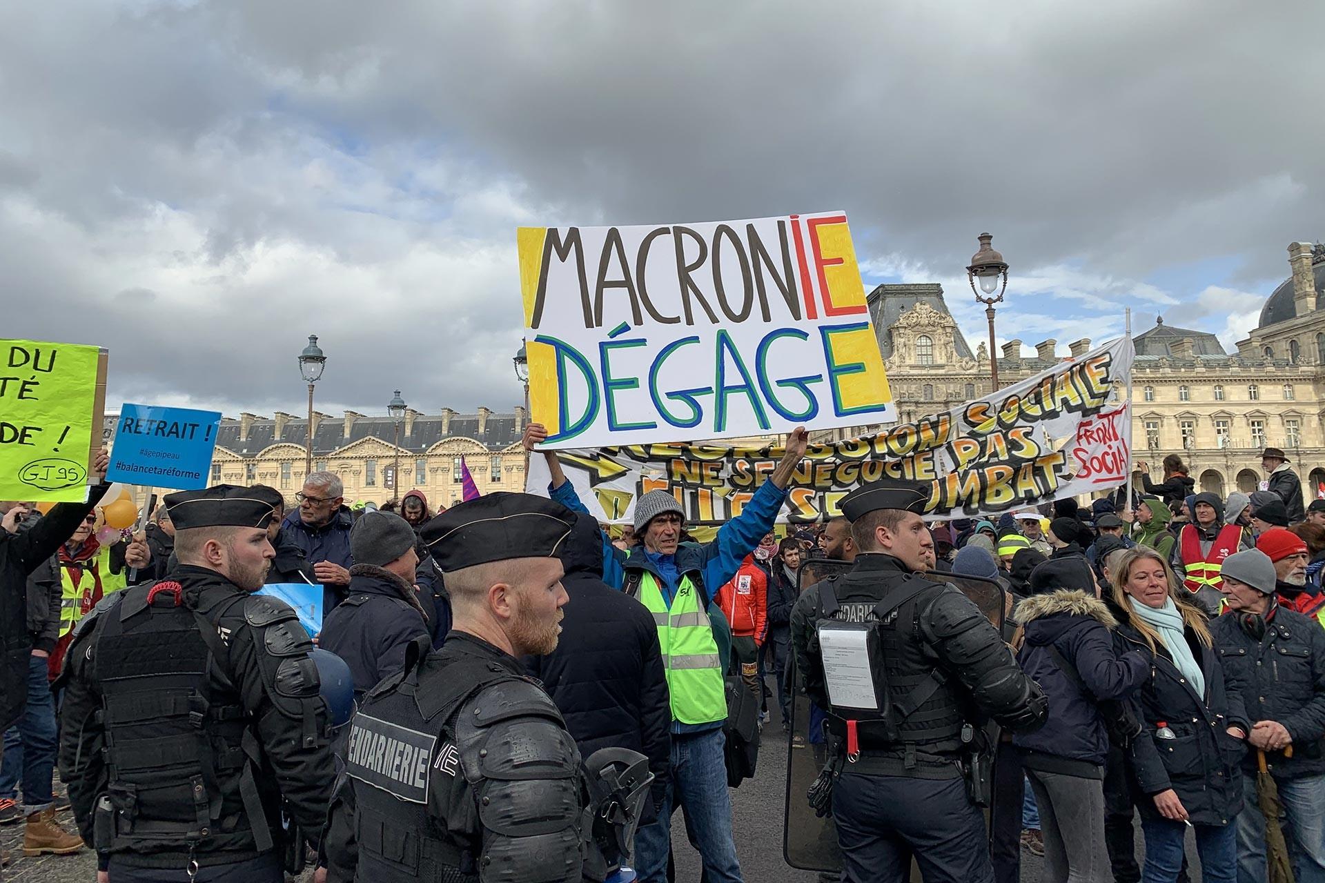 Macron istifa yazılı bir döviz taşıyan kişi ve çok sayıda eylemci ve polisler.