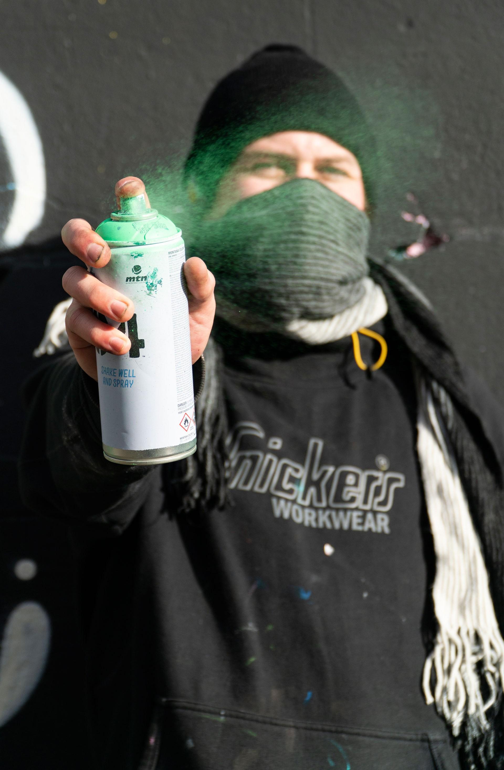 Dublinli graffiti sanatçısı Kurb, kameraya doğru sprey boya sıkıyor.