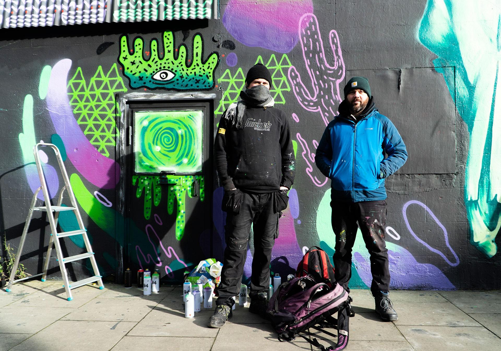Dublinli graffiti sanatçıları Kurb ve James Kirwan çalıştıkları duvarın önünde poz veriyor.