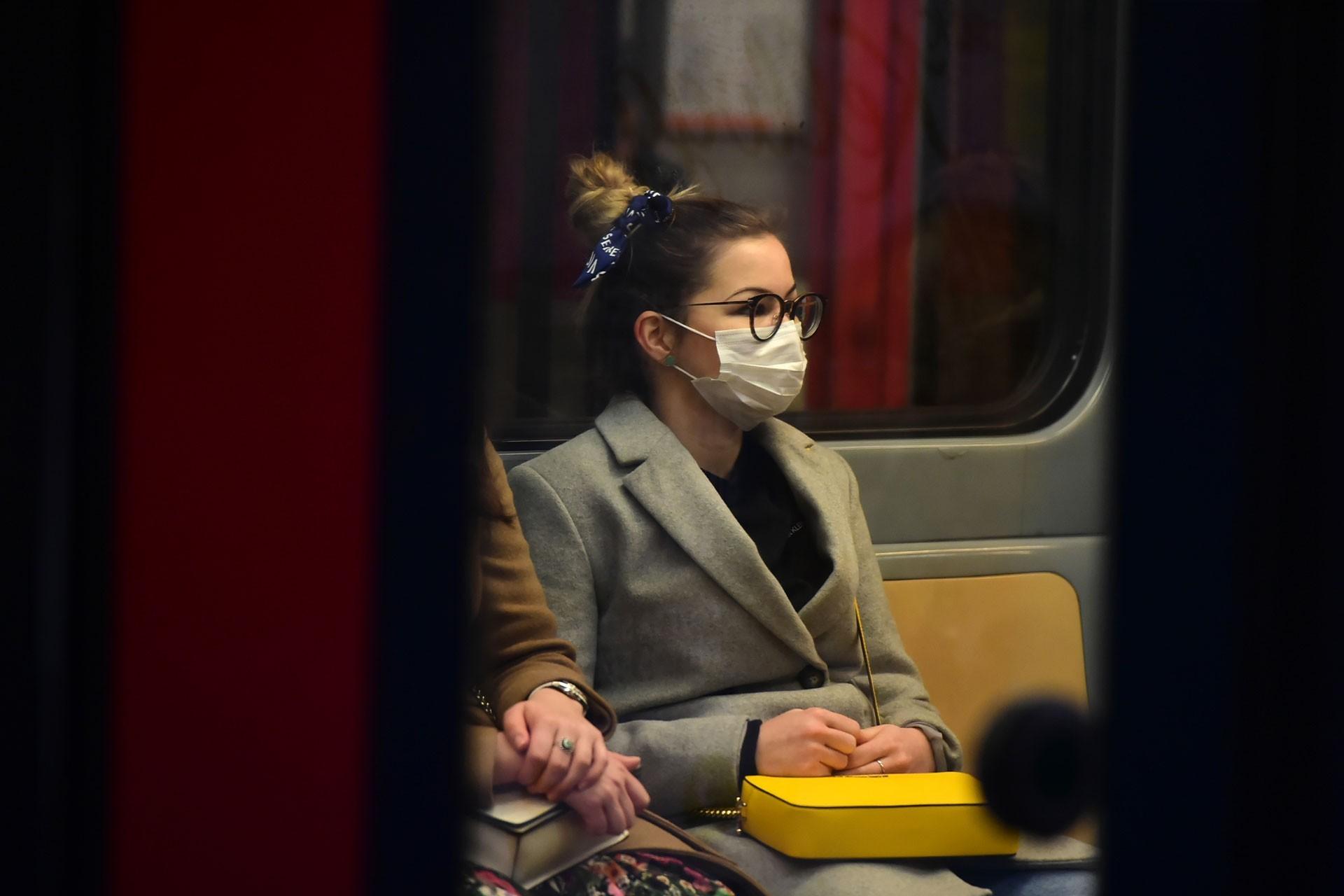Metroda oturan, yüzü maskeli bir kadın