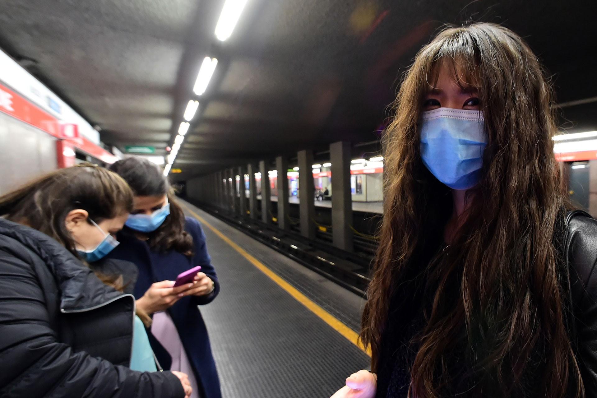 Metro istasyonunda bekleyen yüzü maskeli 3 Çinli kadın