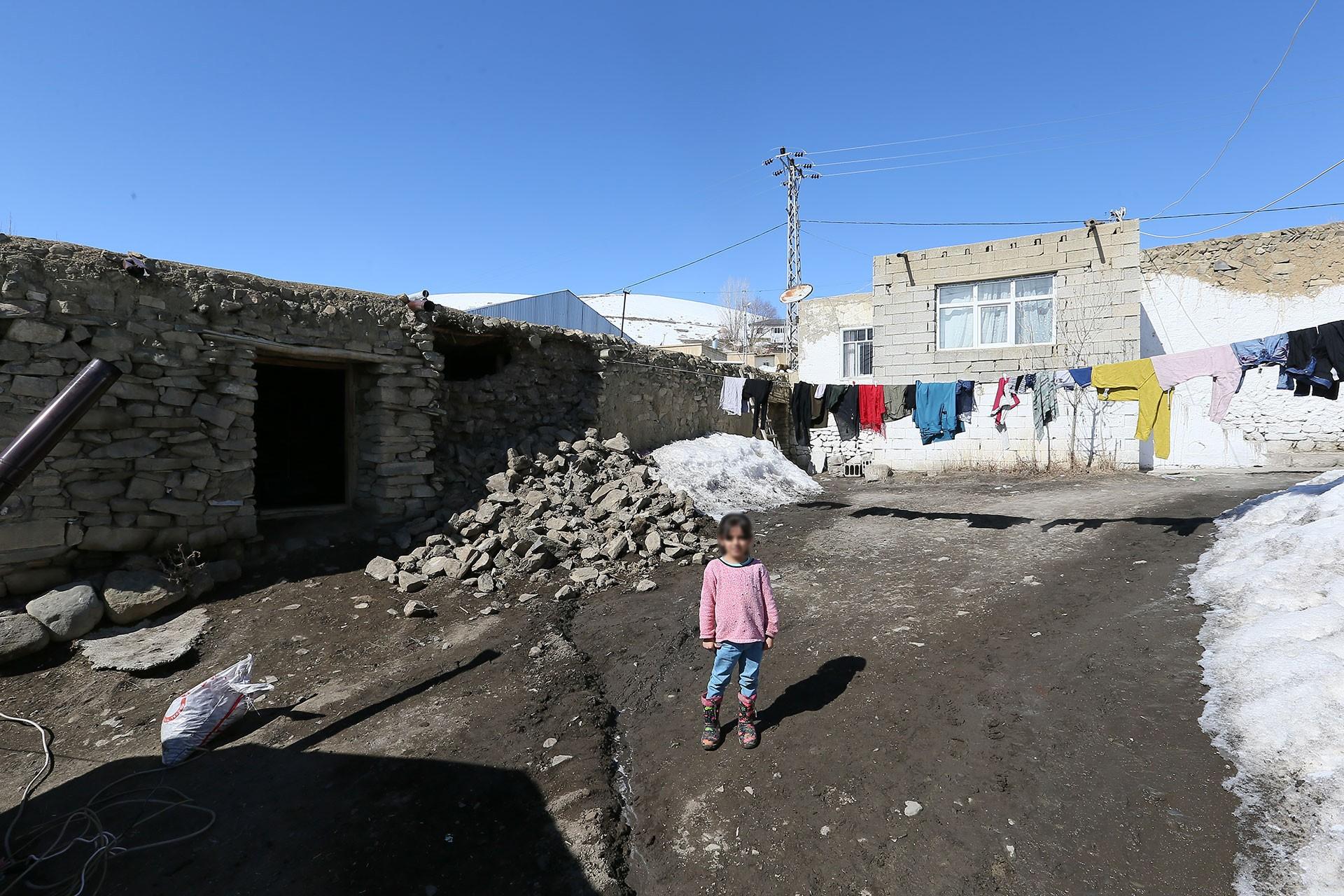 Depremde yıkılan ahır (solda) ve depremzede çocuk