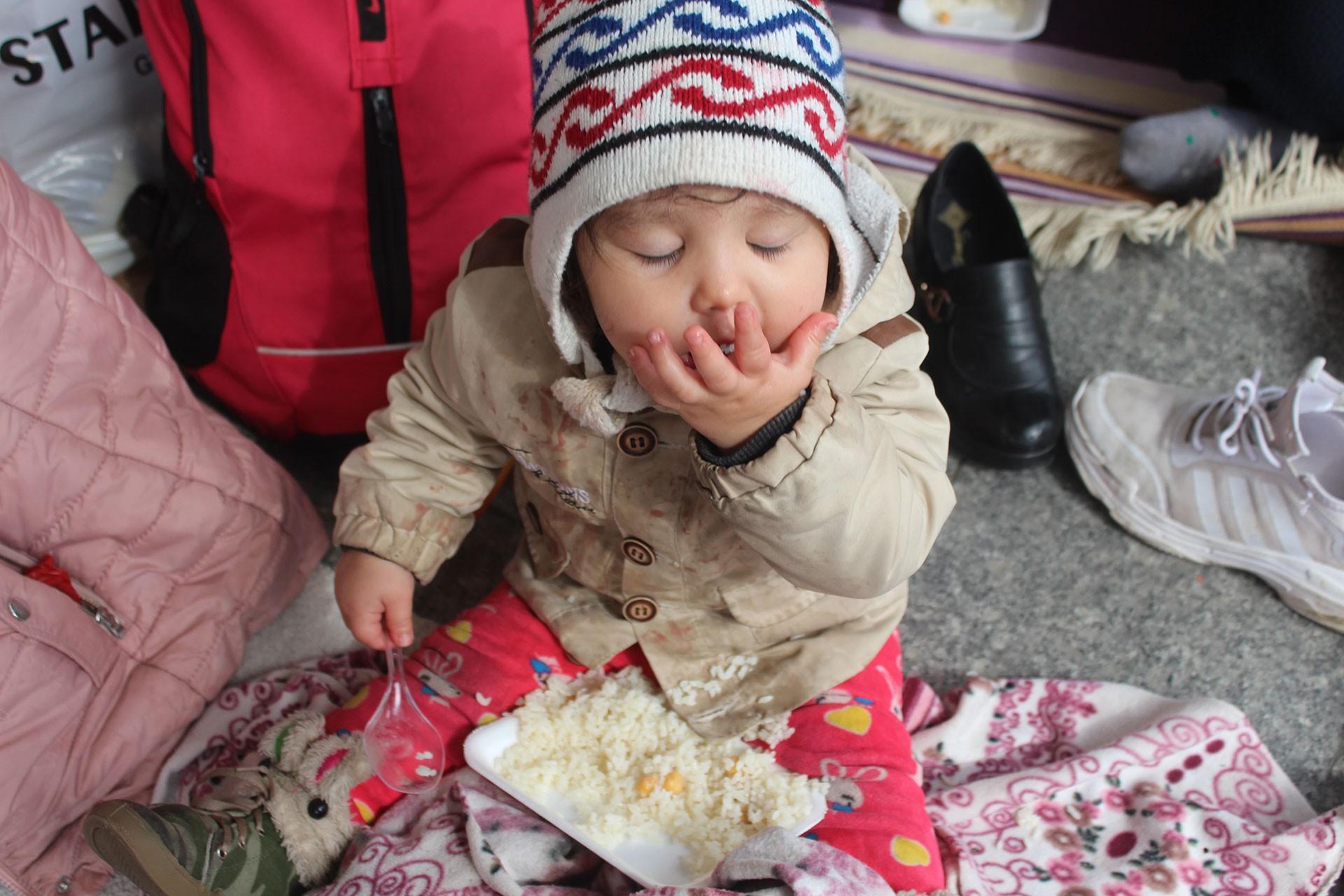 Yerde, betonda incecik battaniyenin üstünde oturan, yemek yiyen mülteci bir bebek.