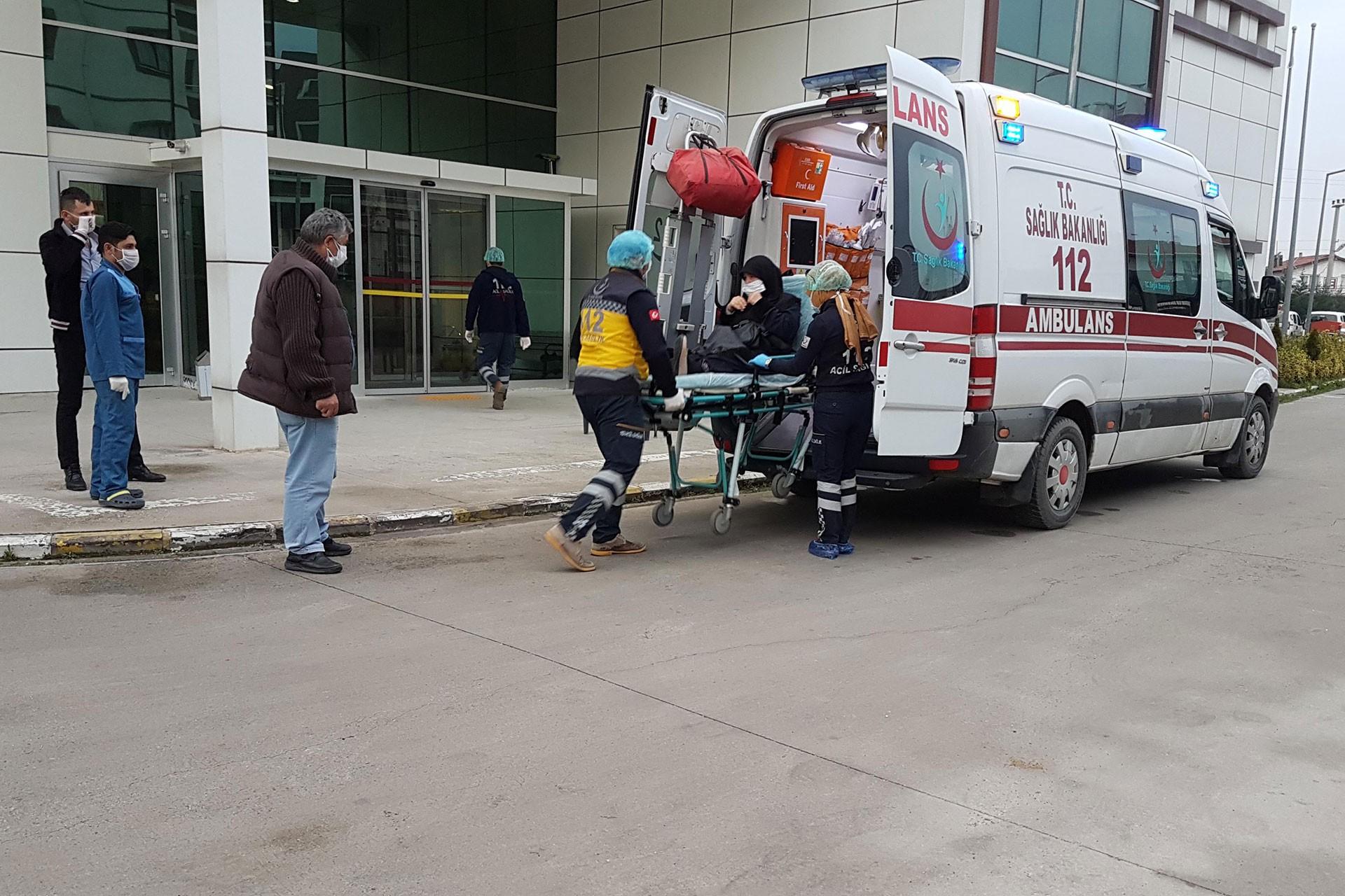 Koronavirüs şüphesiyle hastaneye kaldırılan kadın, sağlık çalışanları ve ambulans (sağda)