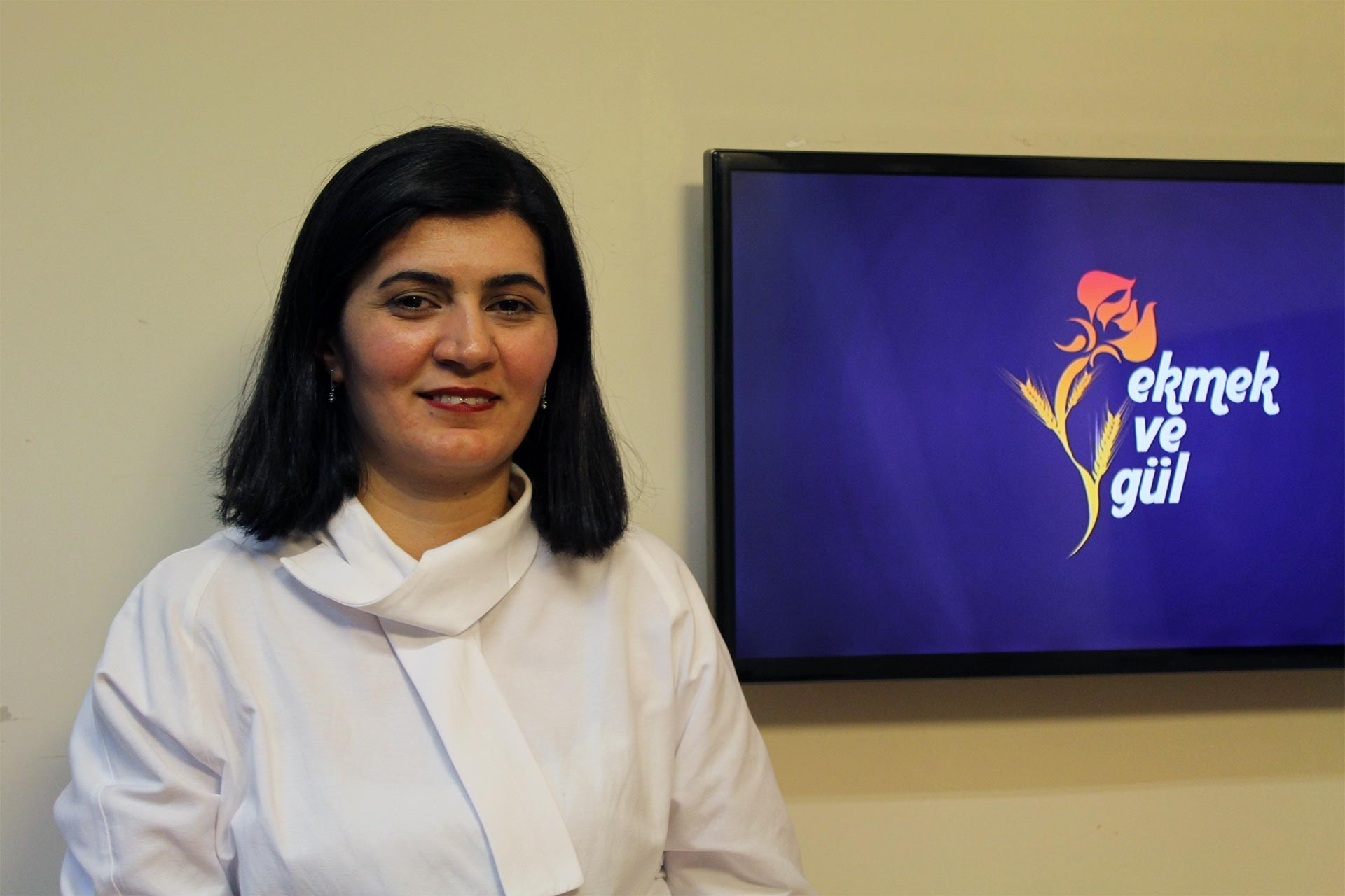 Avukat Yelda Koçak'ın Ekmek ve Gül logosu önünde verdiği pozu
