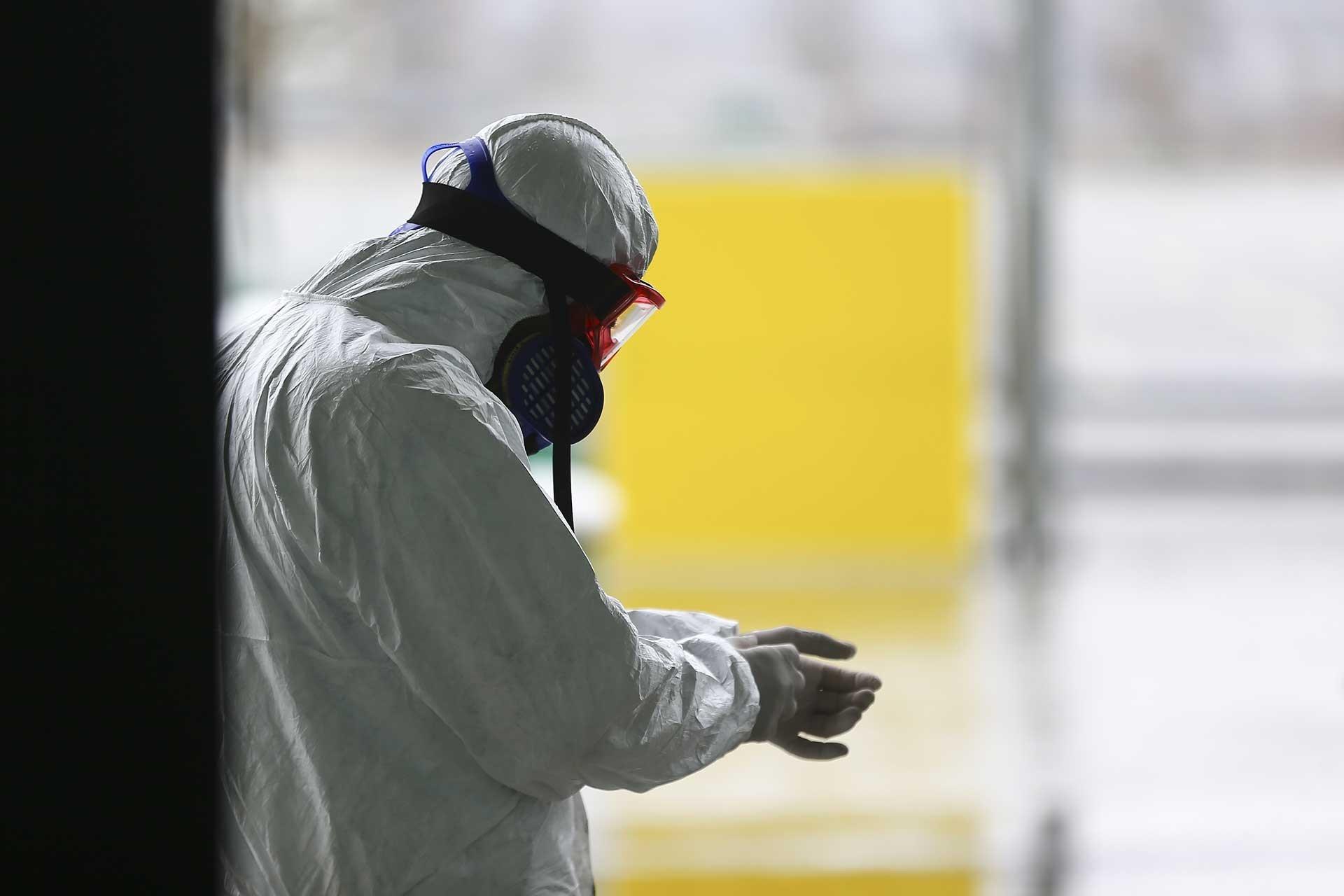 Özel kıyafetlerle Kovid-19'a karşı dezenfekte çalışması yapan bir görevli.