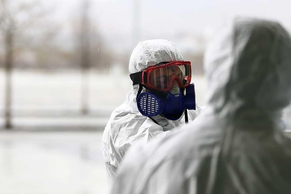 Kovid-19 tedbirleri kapsamında özel kıyafetlerle dezenfekte çalışması yapan ekipler.