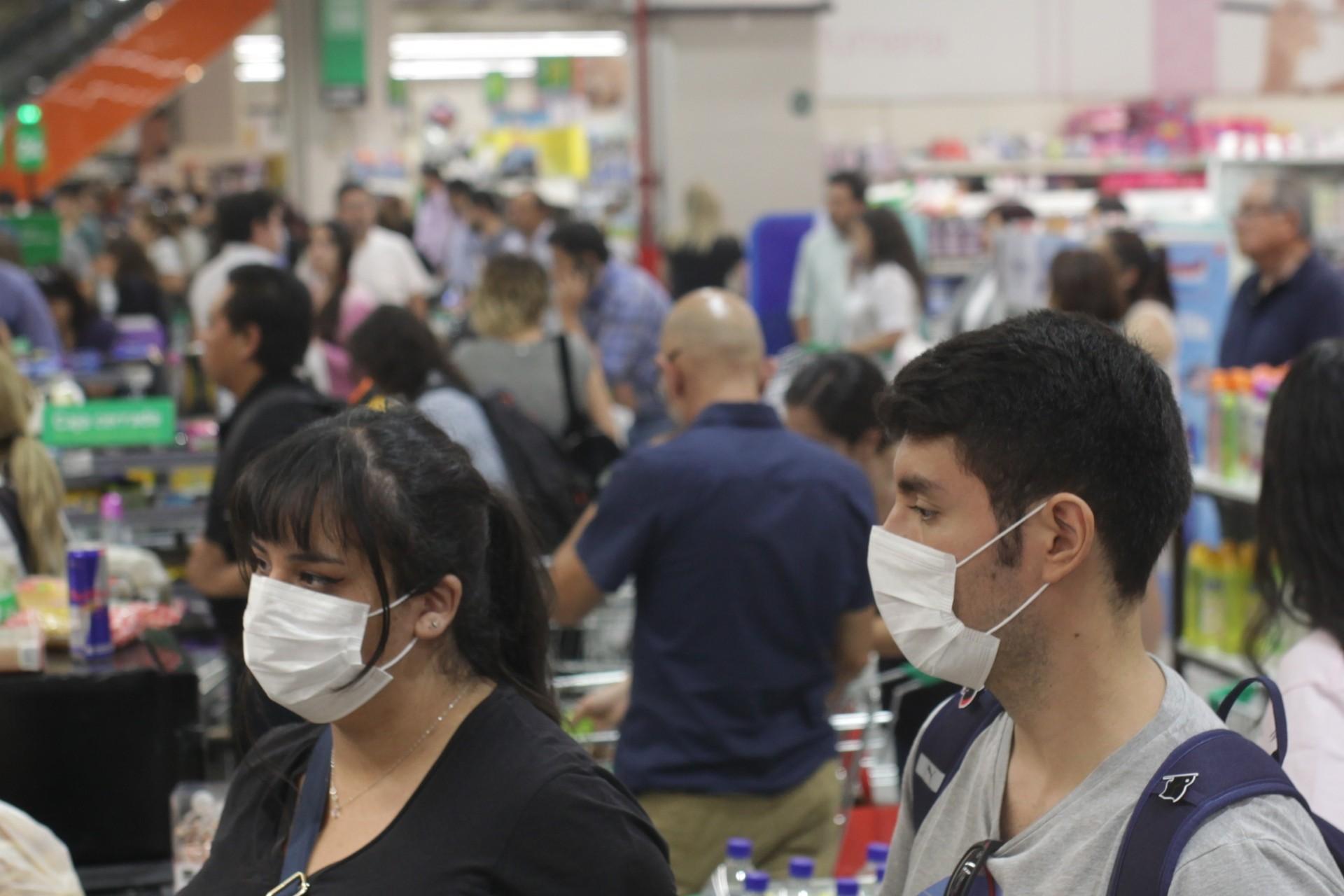 Şili'de ağızlarında maske olan insanlar marketten alışveriş yapıyor.