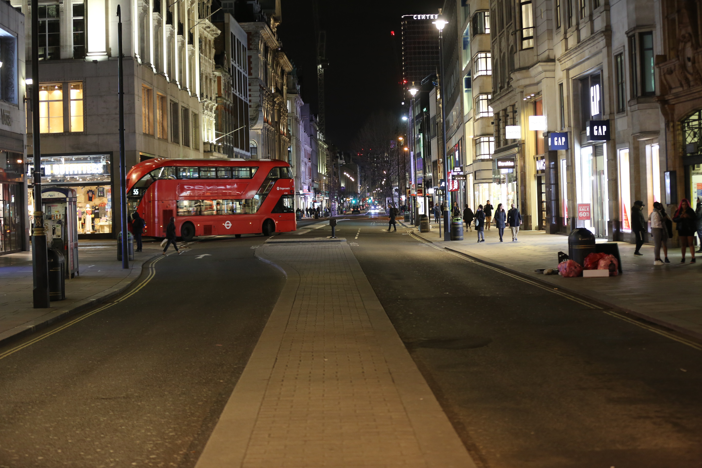 londrada bir caddede yürüyen insanlar ve kırmızı otobüs