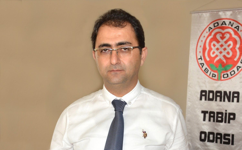 Ahmet Hilali'in Adana Tabip Odası flaması önünde verdiği poz