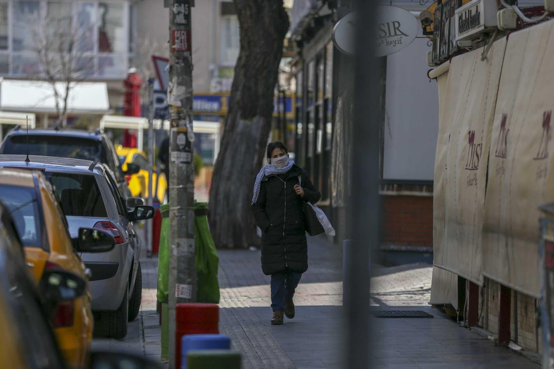 Ankara'da tenha caddede ağzı ve burnu kapalı halde yürüyen bir kadın.
