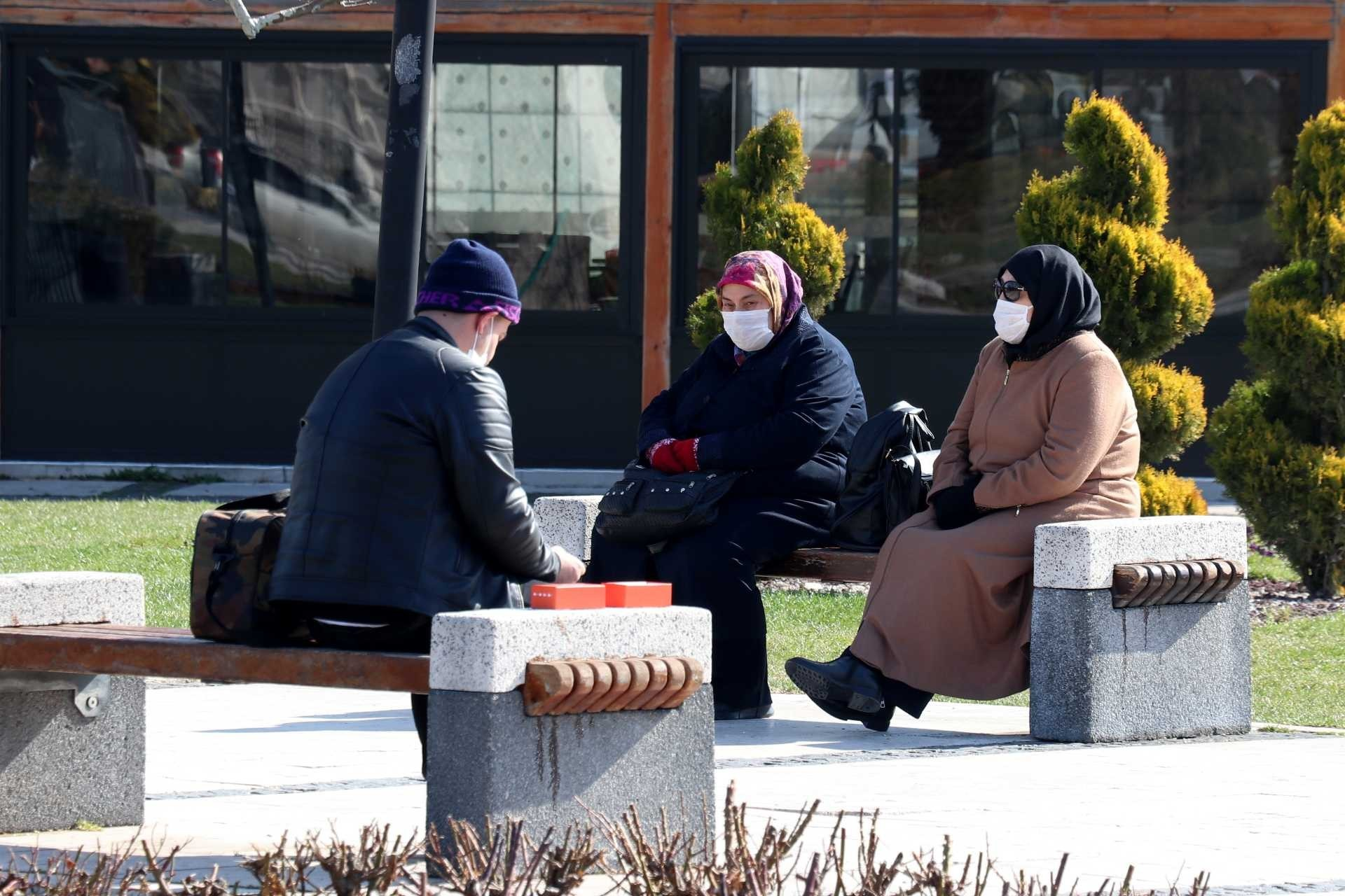 Sivas'ta kent meydanında banklarda oturan ve koronavirüs (Kovid-19) salgını dolayısıyla ağız ve burunlarını maskeyle kapatan insanlar.
