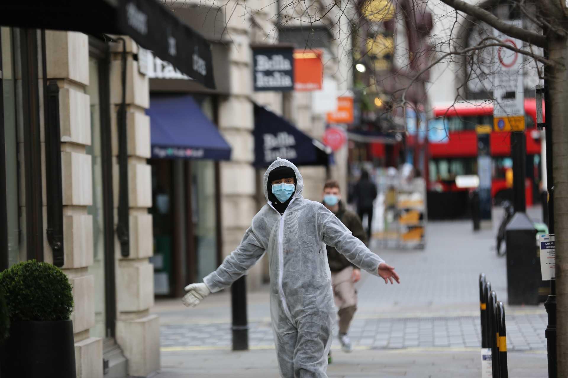 İngiltere'de koronavirüs (Kovid-19) salgını yüzünden boş caddede koruyucu giysi ve maske ile dolaşan bir erkek.