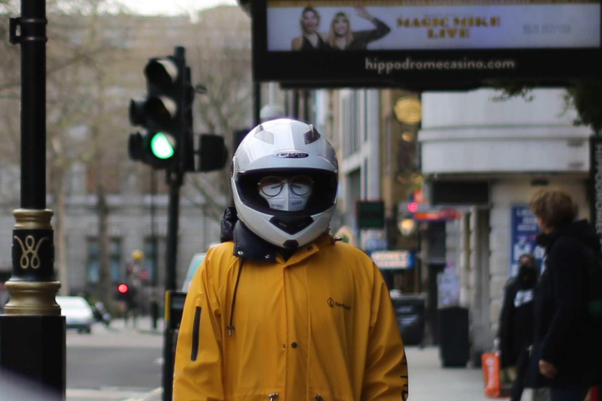 İngiltere'de koronavirüs (Kovid-19) salgını yüzünden boş caddede yüzünde maske ve kafasında motosiklet kaskı ile dolaşan biri.