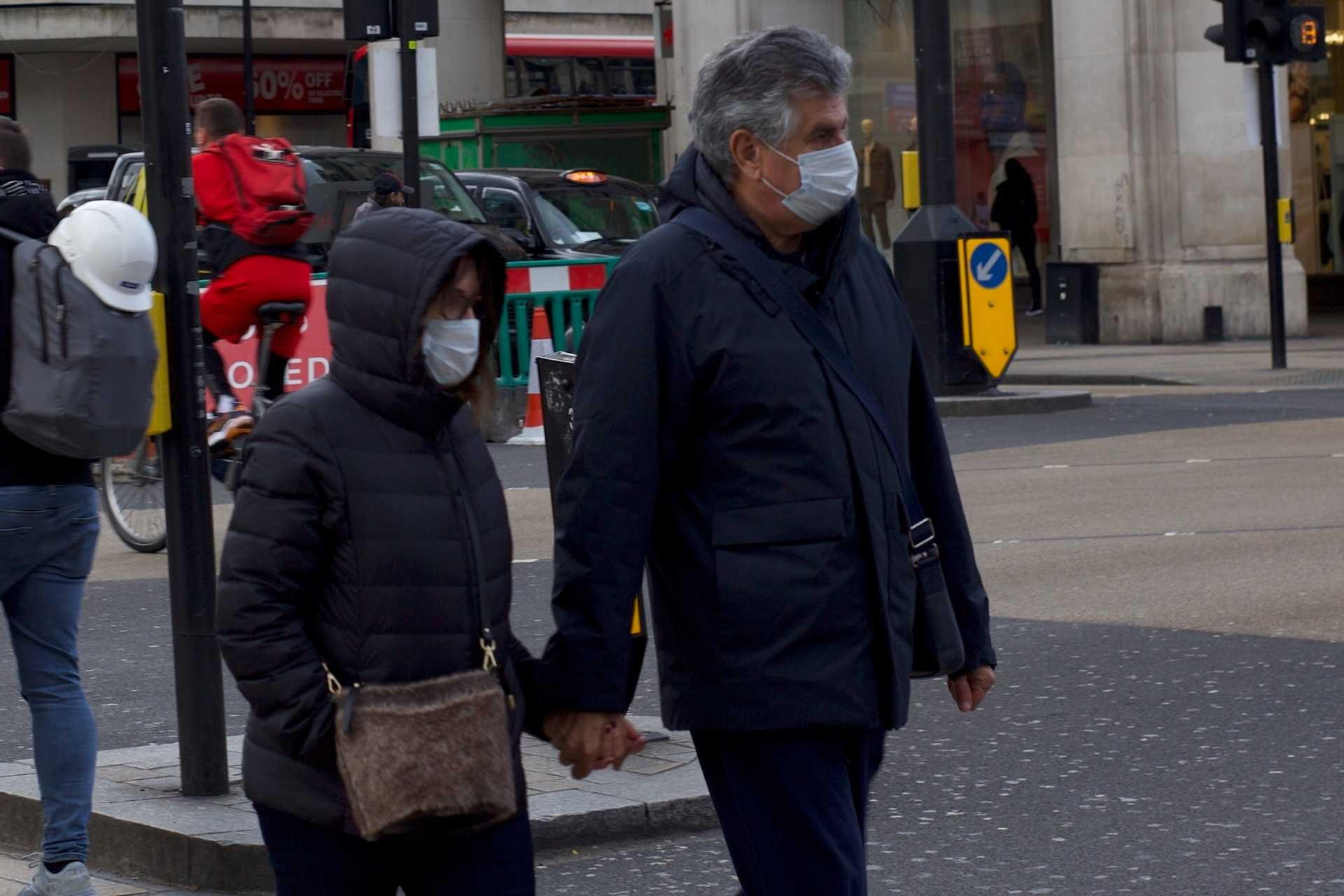 İngiltere'de koronavirüs (Kovid-19) salgını yüzünden yüzlerinden maske ile dolaşan ve el ele tutuşmuş bir erkek ve bir kadın.