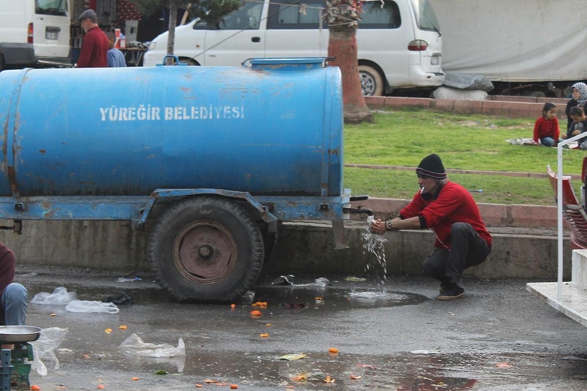Belediyenin su aracından akan suyla ellerini yıkayan yurttaş.