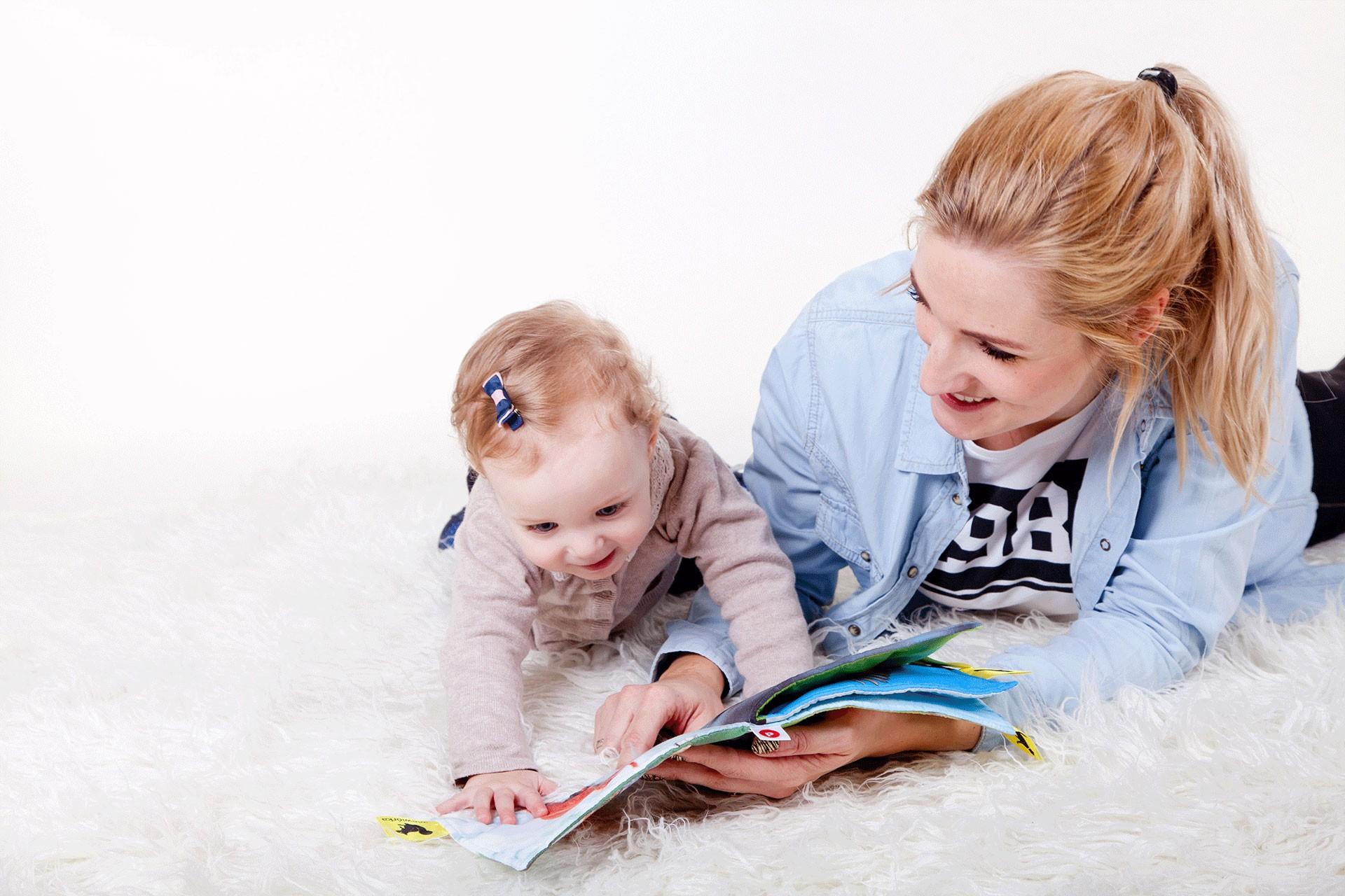 Renkli bir kitapla eğlenen bebek ve anne.